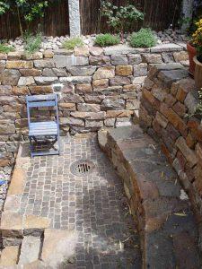 Sitzmauer und Bodenbelag aus Porphyr